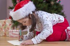 Kleines Mädchen, das Santa Letter vorbereitet Sie die Geschenke s malend lizenzfreie stockfotografie