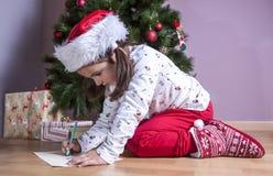 Kleines Mädchen, das Santa Letter vorbereitet Sie die Geschenke s malend lizenzfreies stockfoto