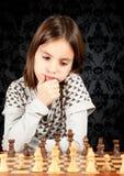 Kleines Mädchen, das Schach spielt Stockfotos