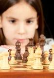 Kleines Mädchen, das Schach spielt Stockfoto