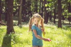 Kleines Mädchen, das Seifenblasen tut Stockbilder