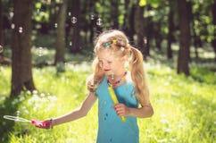 Kleines Mädchen, das Seifenblasen tut Stockfoto