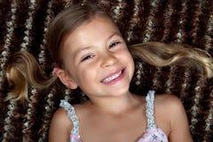 Kleines Mädchen, das sich auf einer Wolldecke und einem Lächeln hinlegt Stockfotografie