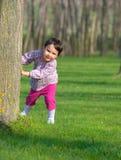 Kleines Mädchen, das sich im Frühjahr hinter einem Baum in einem Wald versteckt Lizenzfreie Stockfotos