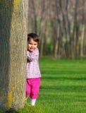 Kleines Mädchen, das sich im Frühjahr hinter einem Baum in einem Wald versteckt Stockfoto