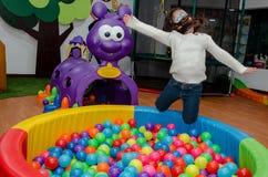 Kleines Mädchen, das sich voll in einem Pool von farbigen Bällen wirft stockfoto