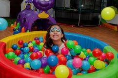 Kleines Mädchen, das sich voll in einem Pool von farbigen Bällen wirft lizenzfreie stockfotos