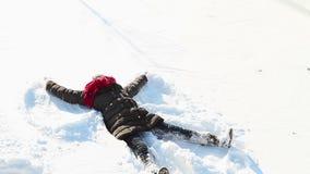Kleines Mädchen, das snowangel macht stock video