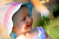 Kleines Mädchen, das Spaß mit einigen Seifenluftblasen hat Lizenzfreie Stockfotos