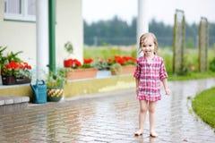 Kleines Mädchen, das Spaß unter dem Regen hat lizenzfreie stockfotografie