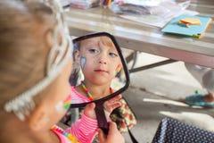 Kleines Mädchen, das Spiegel untersucht Stockfotos