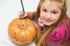 Kleines Mädchen, das spielt, um einen Kürbis für Halloween herzustellen Stockbild