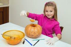 Kleines Mädchen, das spielt, um einen Kürbis für Halloween herzustellen Stockfoto