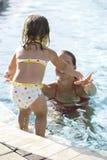 Kleines Mädchen, das springt, um im Swimmingpool zu bemuttern Lizenzfreies Stockfoto