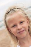Kleines Mädchen, das am Strand im Sommer lächelt Stockfotografie