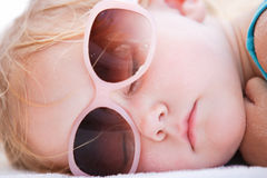 Kleines Mädchen, das am Strand schläft Lizenzfreie Stockfotos