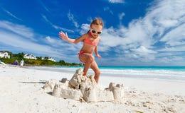 Kleines Mädchen, das am Strand spielt Stockfotografie