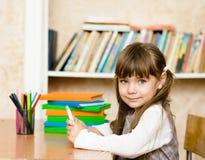 Kleines Mädchen, das Tablet-Computer verwendet Betrachten der Kamera Stockfoto