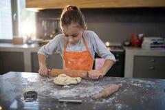Kleines Mädchen, das Teig auf der Küchenarbeitsplatte flachdrückt stockfoto