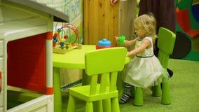 Kleines Mädchen, das am Tisch spielt stock video