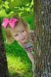 Kleines Mädchen, das um Baum emporragt Lizenzfreies Stockbild