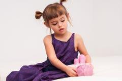 Kleines Mädchen, das um Puppe sich kümmert Stockfoto