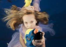 Kleines Mädchen, das underwater mit Wassergewehr schwimmt stockfoto