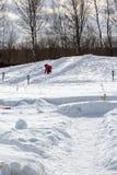 Kleines Mädchen, das unten von einem Schneehügel rollt Stockbilder