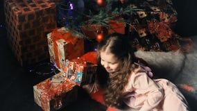 Kleines Mädchen, das unter dem Weihnachtsbaum nahe bei den Geschenken liegt stock footage