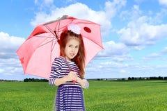Kleines Mädchen, das unter einem Regenschirm sich versteckt Lizenzfreie Stockfotografie