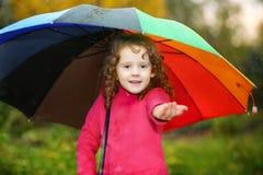 Kleines Mädchen, das unter einem Regenschirm vom Regen sich versteckt Lizenzfreie Stockfotografie