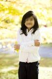 Kleines Mädchen, das unter hellen Herbstblättern steht Lizenzfreies Stockfoto