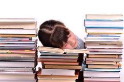 Kleines Mädchen, das unter Stapeln Büchern schläft Lizenzfreie Stockbilder