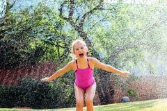 Kleines Mädchen, das unter Wassertropfen schreit Lizenzfreie Stockfotografie