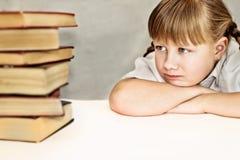 Kleines Mädchen, das unzufrieden Bücher betrachtet Stockfoto