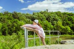 Kleines Mädchen, das verschiedene Übungen auf Metallsperre Park im im Freien am herrlichen sonnigen Tag des Sommers ausdehnt und  Lizenzfreies Stockfoto