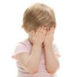 Kleines Mädchen, das Verstecken spielt Stockfotos