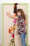 Kleines Mädchen, das versucht, den Wandschrank zu schließen lizenzfreie stockfotografie