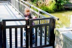 Kleines Mädchen, das versucht, ein geschlossenes hölzernes Tor zu öffnen Lizenzfreie Stockbilder