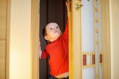 Kleines Mädchen, das versucht, eine Tür zu öffnen Lizenzfreie Stockfotos