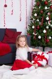 Kleines Mädchen, das in verziertem Wohnzimmer mit Weihnachtsbaum sitzt Stockfoto