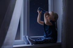 Kleines Mädchen, das voll den Himmel von Sternen betrachtet