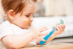 Kleines Mädchen, das von einem Löffel auf blauem Stuhl einzieht lizenzfreie stockbilder