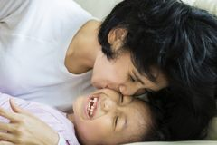 Kleines Mädchen, das von ihrer Mutter geküsst wird Stockfotografie