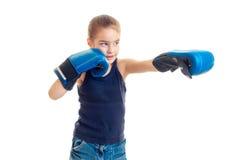 Kleines Mädchen, das vor der Kamera in den Boxhandschuhen und den Blicken in Richtung zu steht Lizenzfreie Stockbilder