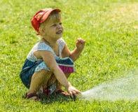 Kleines Mädchen, das während der Bewässerung, Spray hält stockfotos