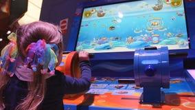Kleines Mädchen, das Wasserwerfer hält und das virtuelle Schießenspiel mit Wasserwerfer auf Spielplatz im Geschäftsmall spielt stock video