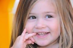 Kleines Mädchen, das weg mit einem Lächeln schaut Stockbild