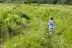 Kleines Mädchen, das weg in Wiese läuft Stockbild