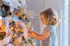 Kleines Mädchen, das Weihnachtsbaum verziert Weihnachten Neues Jahr Viele Feiertagsverzierungen und -geschenke lizenzfreie stockfotos